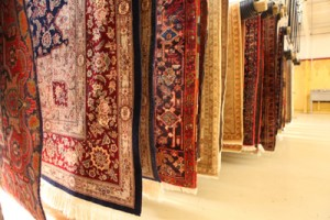 an array of area rugs drying on suspended racks