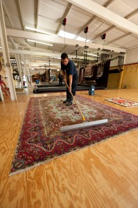 a rug cleaning technician sweeping a large, persian area rug